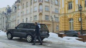 O homem de negócios novo prepara-se à viagem de negócios que põe a mala de viagem dentro do carro filme