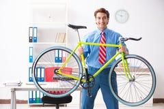 O homem de negócios novo que usa a bicicleta para comutar ao escritório imagem de stock royalty free