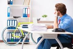 O homem de negócios novo que usa a bicicleta para comutar ao escritório imagem de stock