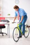 O homem de negócios novo que usa a bicicleta para comutar ao escritório imagens de stock royalty free