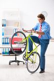 O homem de negócios novo que usa a bicicleta para comutar ao escritório fotografia de stock