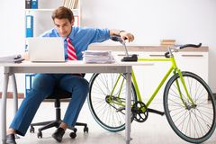 O homem de negócios novo que usa a bicicleta para comutar ao escritório imagens de stock