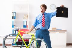 O homem de negócios novo que usa a bicicleta para comutar ao escritório fotos de stock