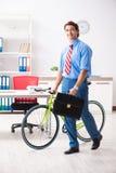 O homem de negócios novo que usa a bicicleta para comutar ao escritório foto de stock