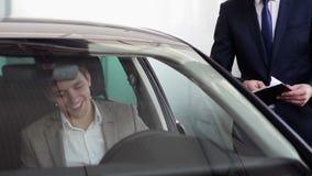 O homem de negócios novo recebeu as chaves a um carro novo video estoque