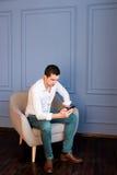 O homem de negócios novo sério escreve mensagens em seu smartphone que senta-se na poltrona imagem de stock