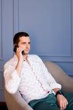 O homem de negócios novo sério fala o telefone celular que senta-se na poltrona foto de stock royalty free