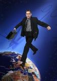 O homem de negócios novo salta através do mundo imagens de stock royalty free