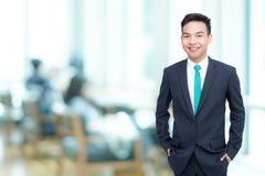 O homem de negócios novo sorri no escritório Imagem de Stock