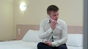 O homem de negócios novo tenso tem um telefonema sério através da linha terrestre que senta-se na sala de hotel Fotografia de Stock Royalty Free