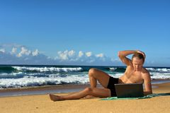 O homem de negócios novo trabalha com o caderno na praia Fotos de Stock Royalty Free