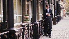 O homem de negócios novo usa o tablet pc na rua vídeos de arquivo