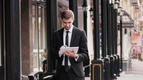 O homem de negócios novo usa a tabuleta digital na rua video estoque