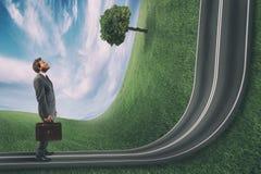 O homem de negócios observa a estrada subida na frente dele Objetivo de neg?cios da realiza??o e conceito dif?cil da carreira fotografia de stock royalty free