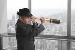 O homem de negócios olha através de um telescópio Fotografia de Stock