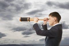 O homem de negócios olha através de um telescópio Imagens de Stock Royalty Free