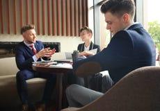 O homem de negócios olha seu relógio de pulso que verifica o tempo Empresário que senta uma reunião e um funcionamento no fundo foto de stock royalty free