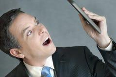 O homem de negócios olha a tabuleta no incrédulo Imagens de Stock Royalty Free