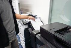 o homem de negócios pôs a folha de papel na bandeja da impressora de escritório para imprimir foto de stock royalty free