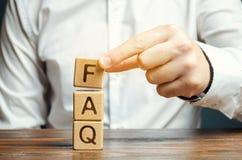 O homem de negócios põe blocos de madeira com a palavra FAQ fez frequentemente perguntas Coleção de perguntas sobre frequentement imagens de stock