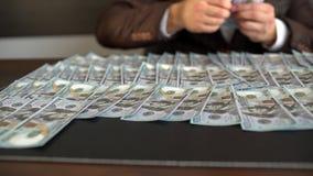 O homem de negócios põe o dinheiro e os dólares sobre a tabela O homem colocou em dólares americanos da tabela O homem do close-u vídeos de arquivo