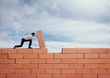 O homem de negócios põe um tijolo para construir uma parede Conceito do negócio, da parceria, da integração e da partida novos foto de stock