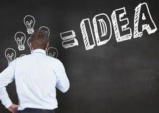 O homem de negócios pensativo que olham bulbos e a ideia text no quadro-negro Foto de Stock Royalty Free