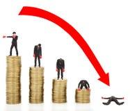 O homem de negócios perde moedas com uma seta vermelha que vai para baixo Fotografia de Stock