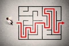 O homem de negócios perdido encontrou a maneira no labirinto com seta vermelha fotografia de stock