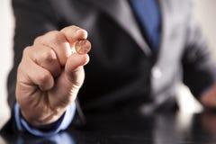 O homem de negócios prende a moeda de um centavo Imagens de Stock
