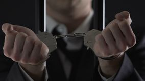 O homem de negócios prendido na exibição da cela algema o close up, fraude financeira video estoque