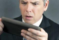 O homem de negócios preocupado olha a tabuleta Imagens de Stock Royalty Free