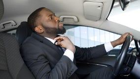 O homem de negócios presumido que senta-se no carro, olhando no espelho para smarten amarra acima fotografia de stock