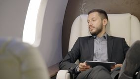 O homem de negócios principal seguro do diretor do banqueiro senta-se para baixo na cadeira do avião, toma a tabuleta, olha para  vídeos de arquivo