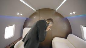O homem de negócios principal seguro novo do diretor do banqueiro está falando no telefone, andando no interior do avião video estoque