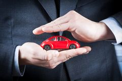 O homem de negócios protege com suas mãos um carro vermelho, conceito para o seguro, compra, aluguer, combustível ou serviço e cus fotos de stock