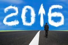 O homem de negócios que anda na estrada asfaltada com sinal 2016 da seta nubla-se Fotografia de Stock