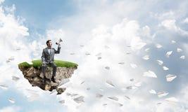 O homem de negócios que anuncia algo em planos do altifalante e do papel voa ao redor Imagens de Stock Royalty Free