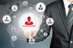 O homem de negócios que aponta em ACCIONISTAS assina na tela virtual Foto de Stock