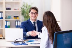 O homem de negócios que discute problemas de saúde com o doutor fotografia de stock royalty free