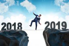 O homem de negócios que equilibra entre 2018 e 2018 fotos de stock royalty free