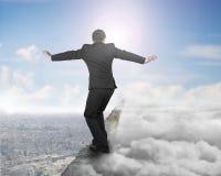 O homem de negócios que equilibra no cume concreto com luz solar do céu nubla-se Imagens de Stock