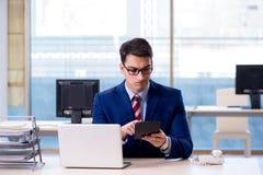 O homem de negócios que faz cálculos para a declaração de rendimentos anual foto de stock