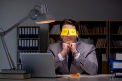 O homem de negócios que fica tarde para classificar para fora prioridades imagem de stock royalty free