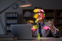 O homem de negócios que fica tarde para classificar para fora prioridades foto de stock royalty free