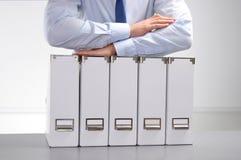 O homem de negócios que guarda arquivos de dados na pasta arquiva o fundo Fotografia de Stock Royalty Free