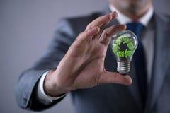 O homem de negócios que guarda a lâmpada no conceito verde do ambiente Imagens de Stock Royalty Free