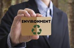 O homem de negócios que guarda a mensagem do cartão recicla, reduz-se, reutiliza-se Conceito Imagem de Stock