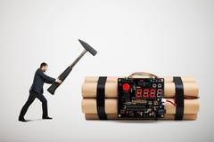 O homem de negócios que guarda o martelo grande e apronta-se a desactivar a bomba grande imagens de stock royalty free