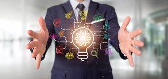 O homem de negócios que guarda um conceito da ideia da lâmpada do bulbo com começa acima o ícone Fotos de Stock Royalty Free